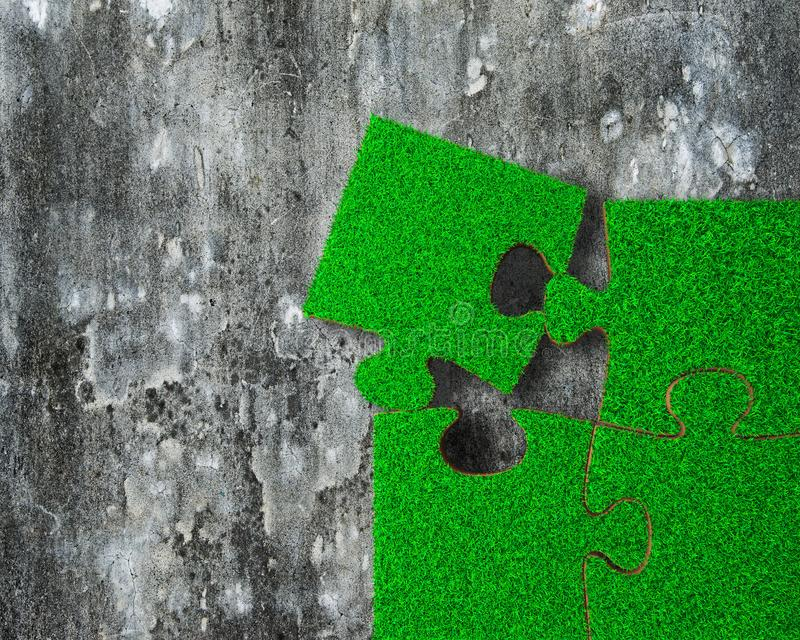 Four jigsaw puzzles with green grass on concrete floor. Jigsaw puzzles made out of green grass, on grunge grey concrete floor background stock images