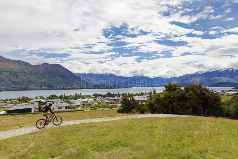Jinete de la bici de montaña en el lago Wanaka foto de archivo