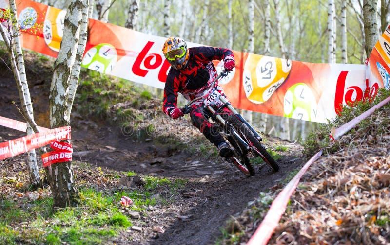 Jinete de la bici de montaña en la acción en una raza en declive fotografía de archivo