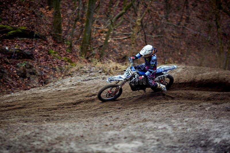 Jinete del motocrós en la acción que acelera la moto después de la esquina en el circuito de carreras fotografía de archivo
