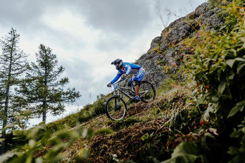 Jinete en la montaña de la bici y la pista en declive del bosque imagenes de archivo