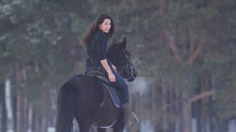 Jinete femenino de pelo largo atractivo que monta un caballo negro a través de las derivas profundas en el campo, vista posterior fotografía de archivo
