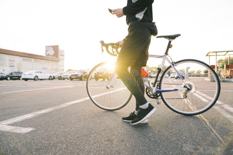 Jinete masculino con una bicicleta en el fondo de la puesta del sol El ciclista del hombre monta una bici en la ciudad imagen de archivo libre de regalías