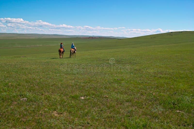 Jinetes de lomo de caballo en prado imágenes de archivo libres de regalías
