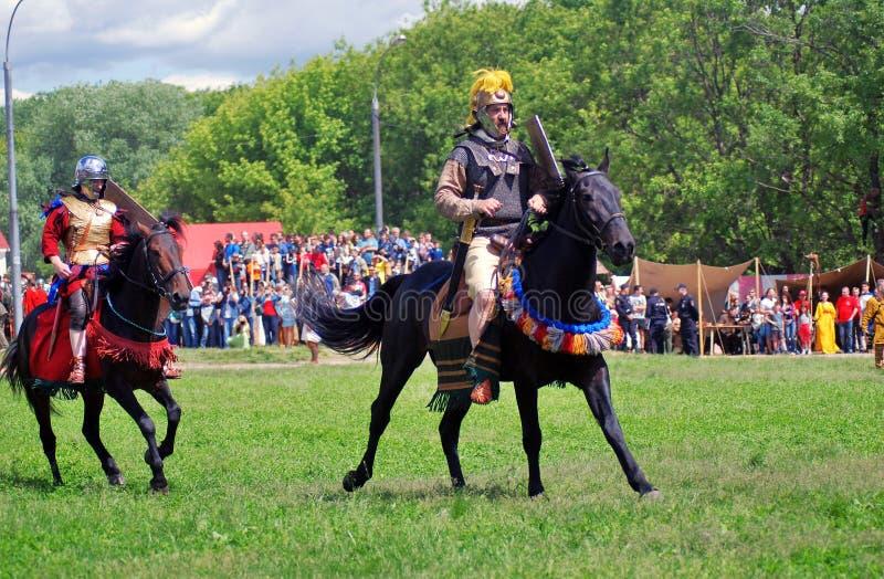 Jinetes del caballo en el campo de batalla imagen de archivo
