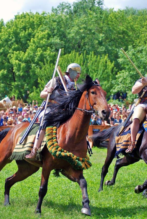 Jinetes del caballo en el campo de batalla foto de archivo