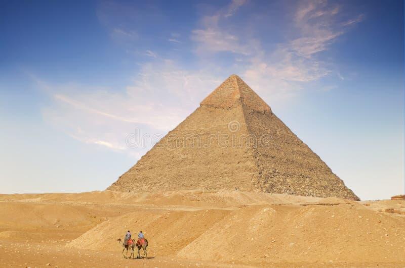 Jinetes del camello que cruzan el desierto cerca de la gran pirámide imagen de archivo libre de regalías