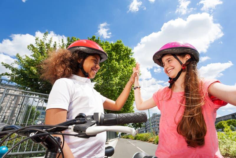 Jinetes felices de la bici que dan el alto cinco después de competir con imagen de archivo