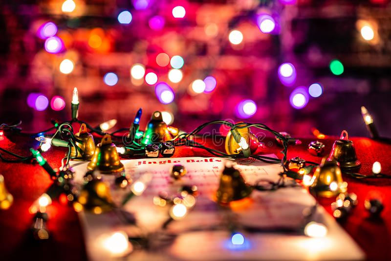 Jingle Bells Sheet Música iluminada por luzes de Natal, cercada por vários sinos Profundidade suave do campo com um poste pesado fotos de stock royalty free