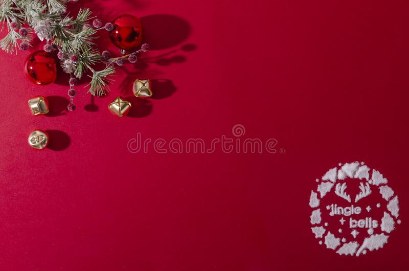 Jingle bells written in snow. Jingle bells logo designed from snow represents the holiday season on a red flat lay concept with Christmas element balancing the stock photos