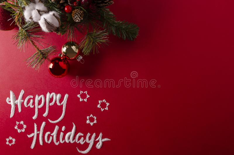 Jingle bells written in snow. Jingle bells logo designed from snow represents the holiday season on a red flat lay concept with Christmas element balancing the stock image