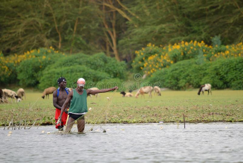 JINJA, OEGANDA - CIRCA-OCT, 2017: Het dagelijkse leven in Jinja De jongeren doet hun het dagelijkse levenswerk bij de rivieroever royalty-vrije stock afbeelding