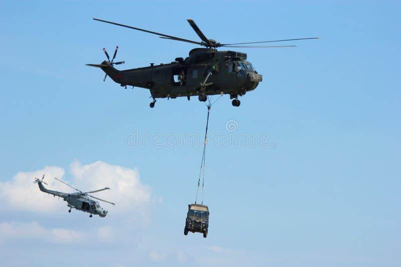 Jipe levando do helicóptero militar fotografia de stock