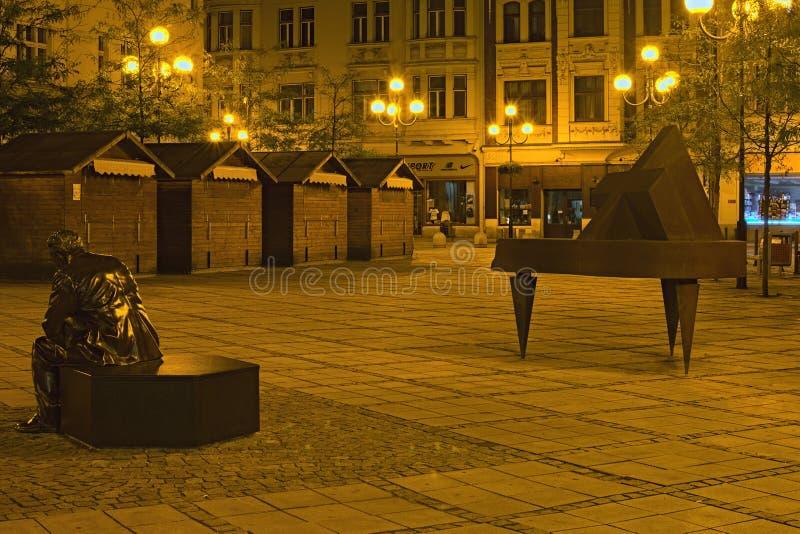 Jirasek广场Jiraskovo namesti在夏夜里 一个人的现代艺术雕塑想法和一架钢琴的 库存照片