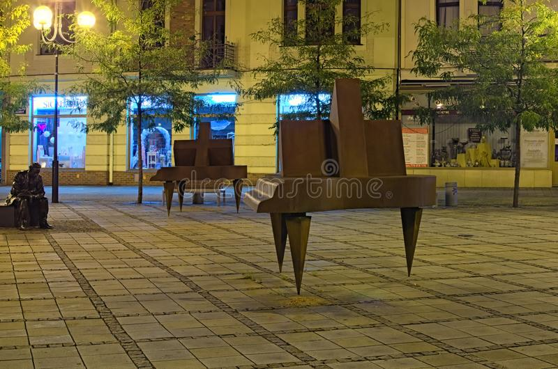 Jirasek square Jiraskovo namesti at summer night. Modern art sculpture of a man in thought and two pianos. Ostrava, Czech Republic- AUGUST 19, 2018: Jirasek royalty free stock images