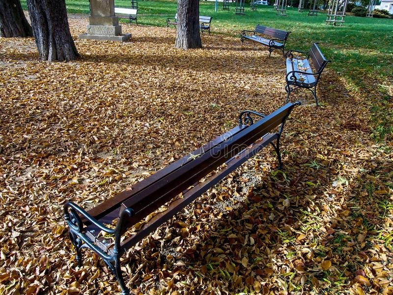 Jirkov, Czech republic - October 22, 2019:  wooden benches in Svojsikovy sady park in centre of autumnal city. Jirkov, Czech republic - October 22, 2019: wooden royalty free stock image