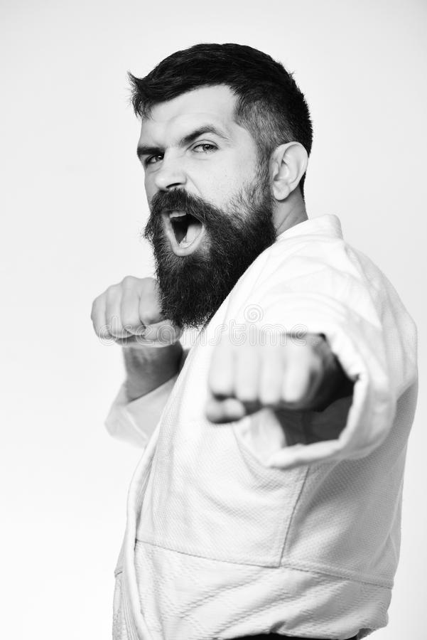 Jiu Jitsu master practices attack or defense posture. Healthy lifestyle and sports concept. Karate man with angry face in uniform. Man with beard in white stock photo
