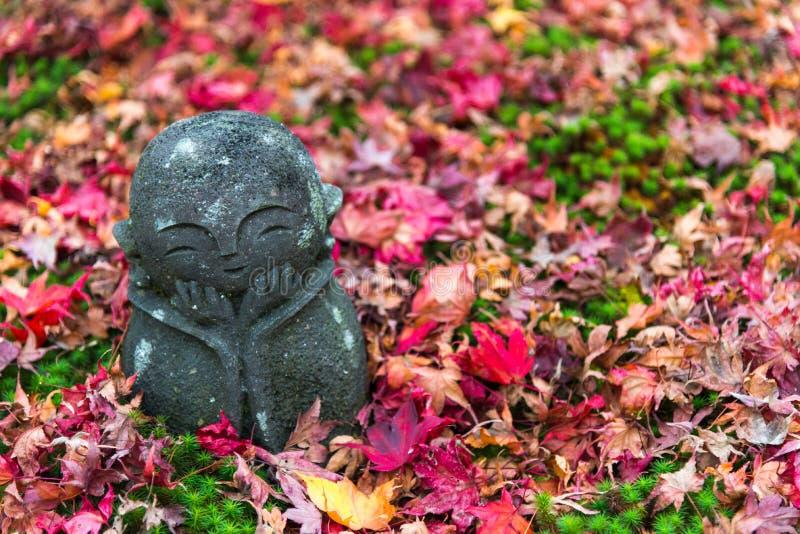 Jizo на красных кленовых листах понижается с красного ковра & x28; немного японский стоковая фотография
