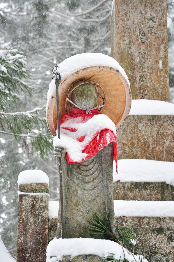 Jizo o estatua de piedra que lleva el delantal rojo debajo de nieve fotografía de archivo libre de regalías