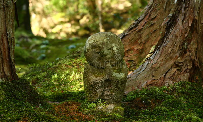 Jizo statue in a buddhist temple. Stone buddhist jizo statue in japanese garden of Sanzen-in temple in Ohara near Kyoto stock photo