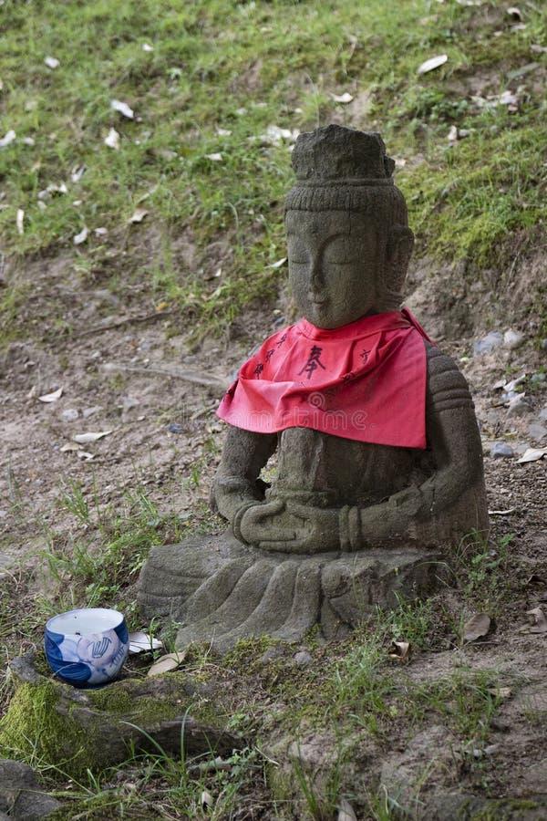 Jizo tallado piedra tradicional con la falda roja honrada y respetada con una taza de agua imagen de archivo