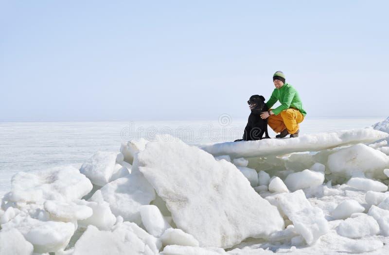 Jjunger erwachsener Mann im Freien mit seinem Hund Spaß in der Winterlandschaft lizenzfreie stockfotos