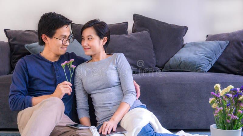 Jjunges asianisches Ehepaar, das sich vor dem Sofa zu Hause auf Valentinstag und Kopierplatz verliebt, verwenden für Paare in ver stockfotos