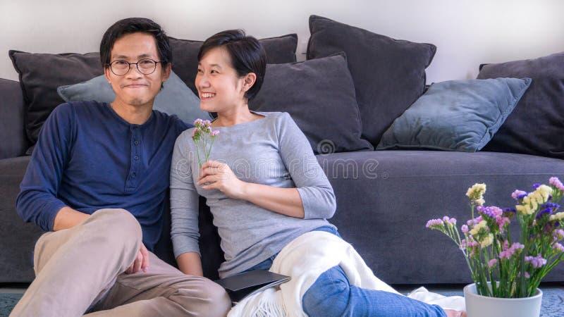 Jjunges asianisches Ehepaar, das sich vor dem Sofa zu Hause auf Valentinstag und Kopierplatz verliebt, verwenden für Paare in ver lizenzfreie stockfotografie