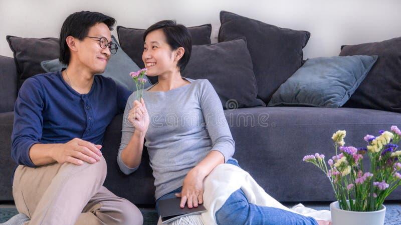 Jjunges asianisches Ehepaar, das sich vor dem Sofa zu Hause auf Valentinstag und Kopierplatz verliebt, verwenden für Paare in ver lizenzfreie stockbilder