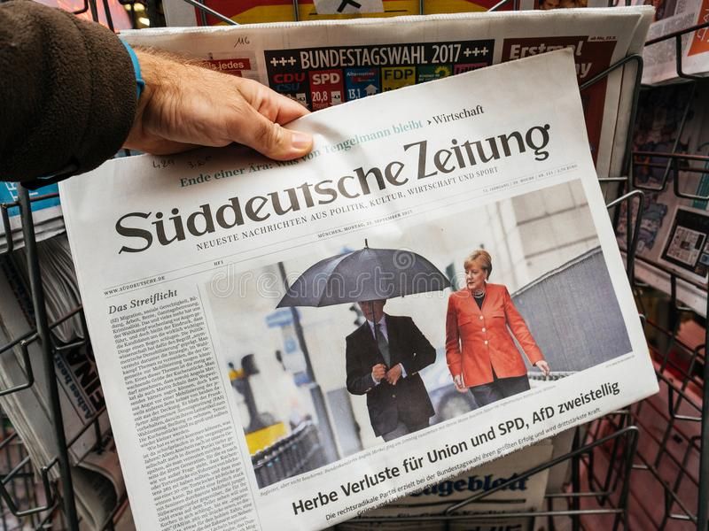 Joachim sauer and Merkel elections day for the Chancellor of Ge. PARIS, FRANCE - SEP 25, 2017: Man buying latest suddeutsche zeitung newspaper with portrait of stock photos