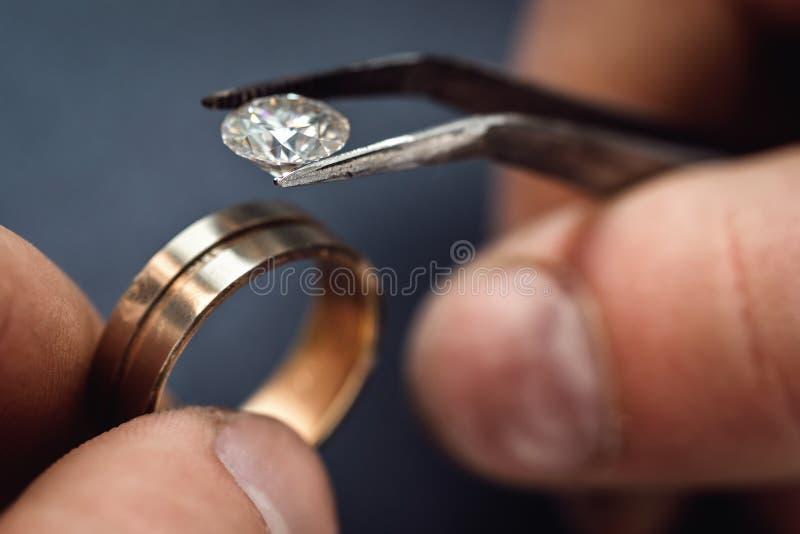 Joalheiro dos trabalhos Cabendo uma pedra preciosa para o futuro do anel dourado imagens de stock