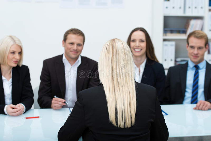 Job applicant in an interview. Young female job applicant in an interview sitting with her back to the camera facing a row of personnel executives royalty free stock photo