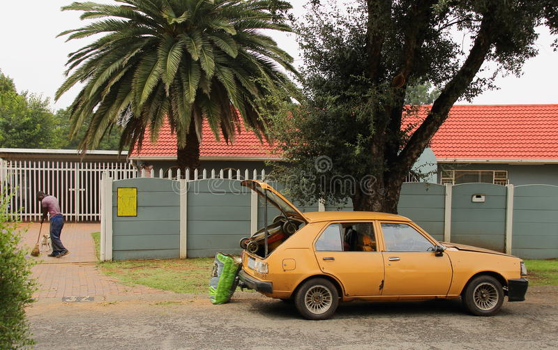 Job creation in post-apartheid South Africa. As a man runs his small garden services business from the back of his old car royalty free stock image
