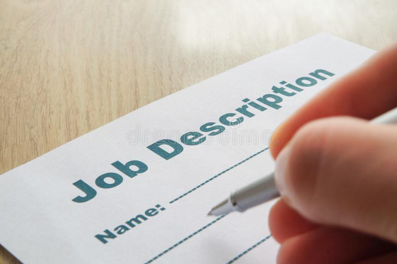 Job Description with Hand and Pen on the table. stock photos