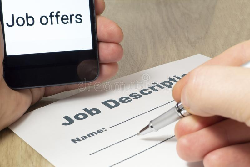 Job Description with Hand, smartphone and Pen on the table royalty free stock photos