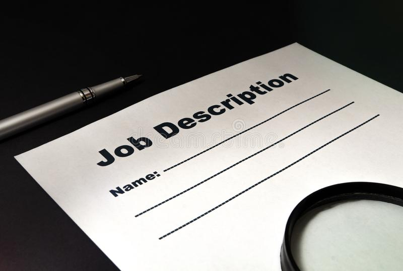 Job description with magnifying glass and pen on black background. Close-up royalty free stock image