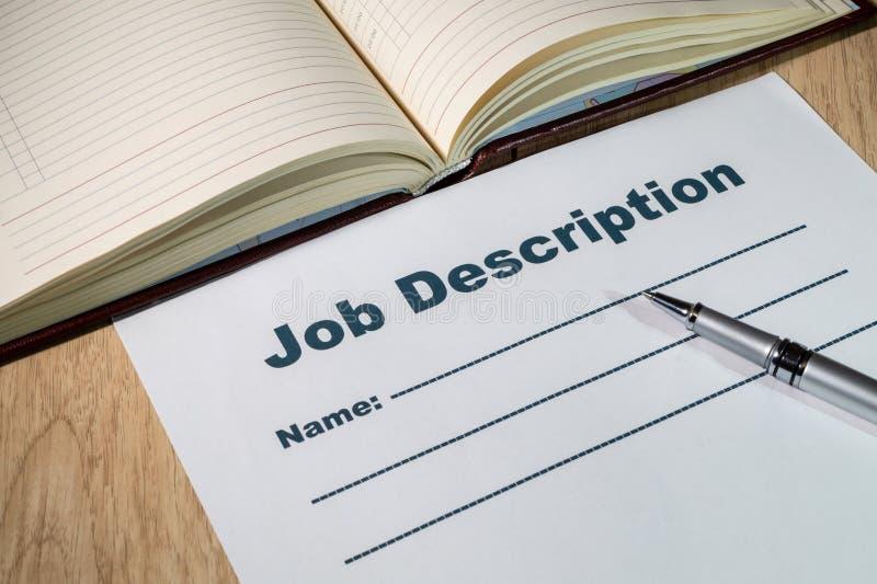 Job description and pen on bright wooden office desk. Blank sheet of Job description and pen on bright wooden office desk stock photography