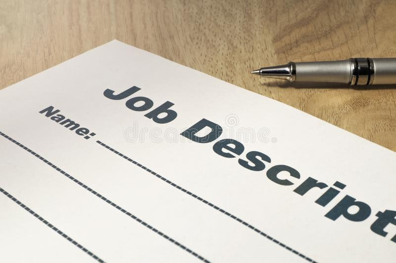 Job Description with Pen on the table close up.. Job Description with Pen on the wooden table close up stock photography