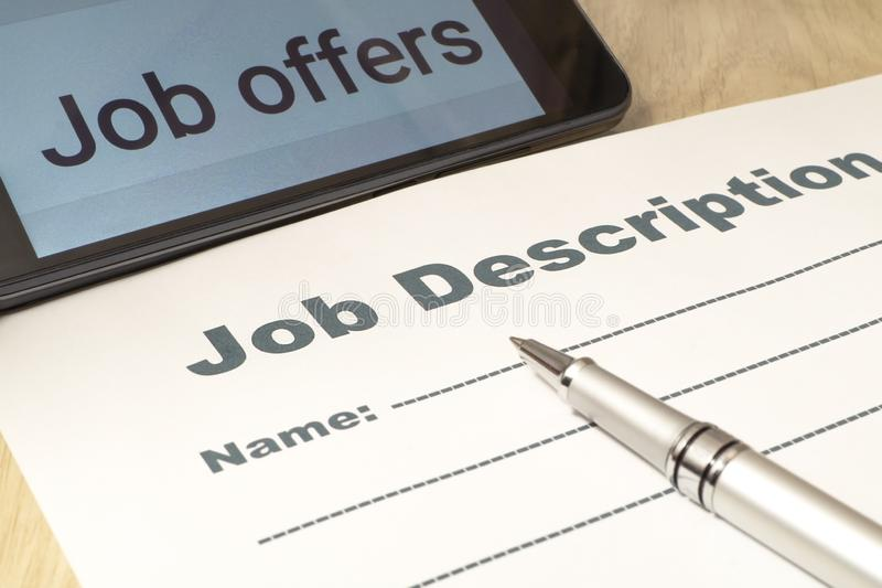 Job Description with smartphone and Pen on the table. Close up royalty free stock photos