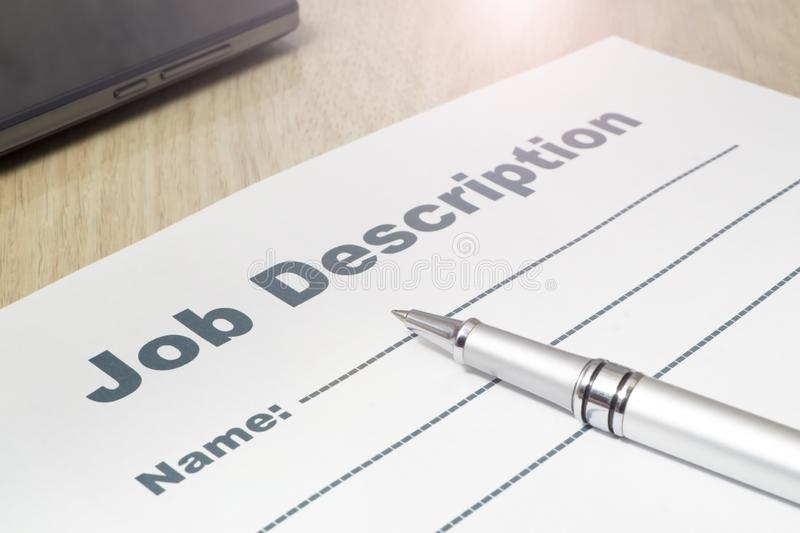 Job Description with smartphone and Pen on the table. Job Description with smartphone and Pen on the table close up royalty free stock image