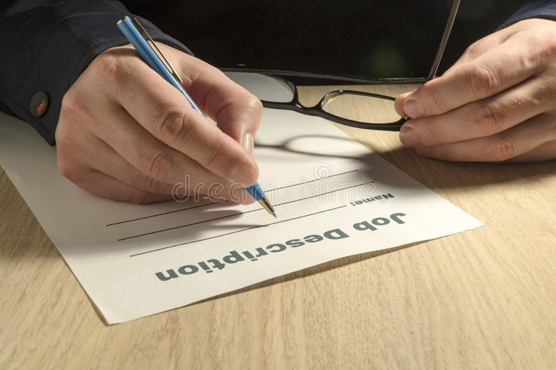 A job description template to fill out with pen and hands. On the office desk close up stock photography