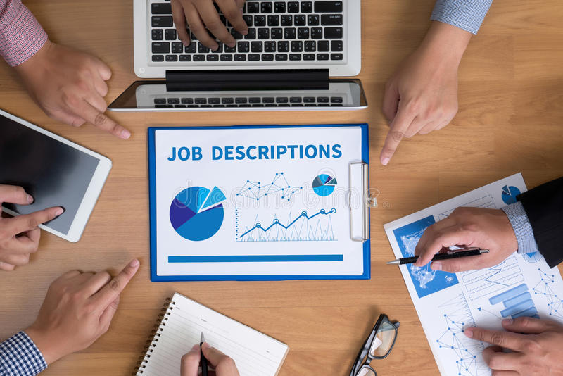 JOB DESCRIPTIONS. Business team hands at work with financial reports and a laptop, top view royalty free stock photo