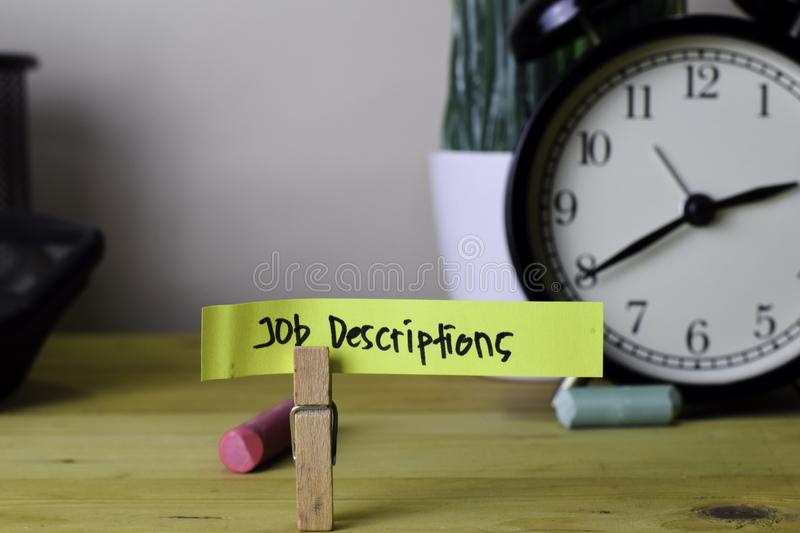 Job Descriptions. Handwriting on sticky notes in clothes pegs on wooden office desk royalty free stock photography