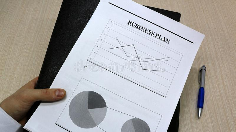 Job with finances in the office on a laptop,the employee holds paper with the inscription business plan.Busines new idea. Job with finances in the office on a royalty free stock photo