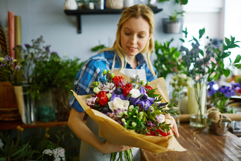Job of florist. Young florist looking at arranged bouquet in her hands stock images