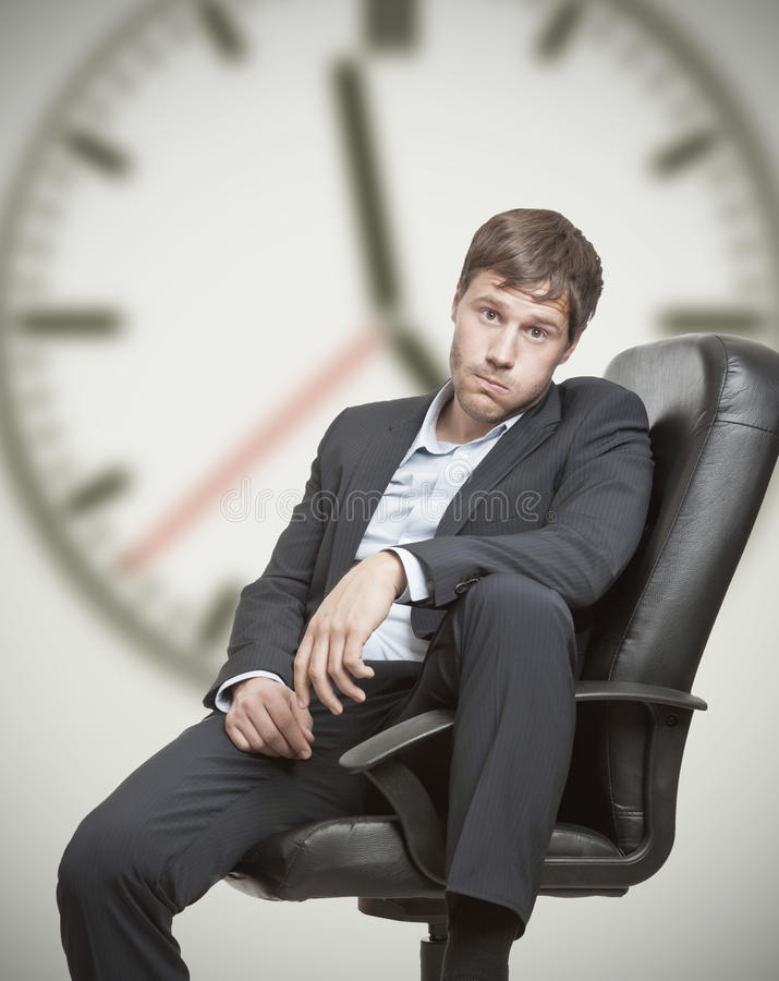Job frustration. Frustrated young business man waiting for the end of the workday stock photos