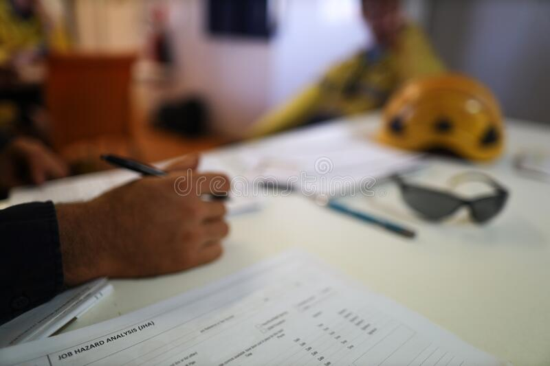Job hazard analysis risk safety assessment high risk work on the table defocused co-worker, supervisor royalty free stock photos
