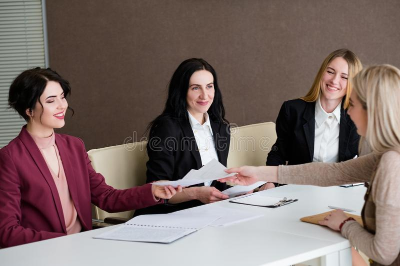 Job hiring hr team work applicant interview. Job hiring. women from hr team smiling to a young work applicant. successful recruitment interview royalty free stock photography