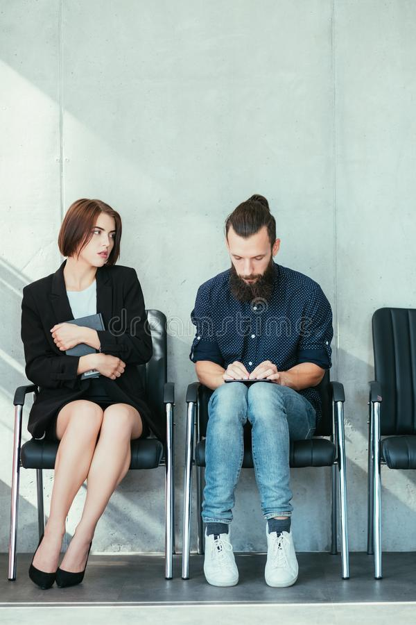 Job hiring rivalry waiting applicant copy space. Job hiring. Rivalry tension. Waiting applicants. Bored woman. Preoccupied man. Copy space on grey background royalty free stock images