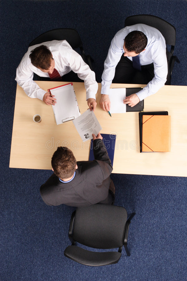 Job Interview. A young man at a a job interview with two interviewers, showing them his resume.Aerial shot taken from directly above the table stock photography